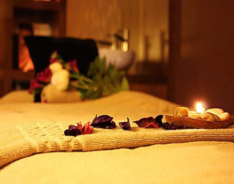 Flower petals and candle on spa bed