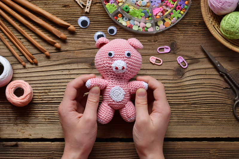 Crochet toy for child. On table threads, needles, hook, cotton yarn.
