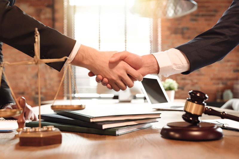 Lawyer and his client handshake. Agreement with attorney in office