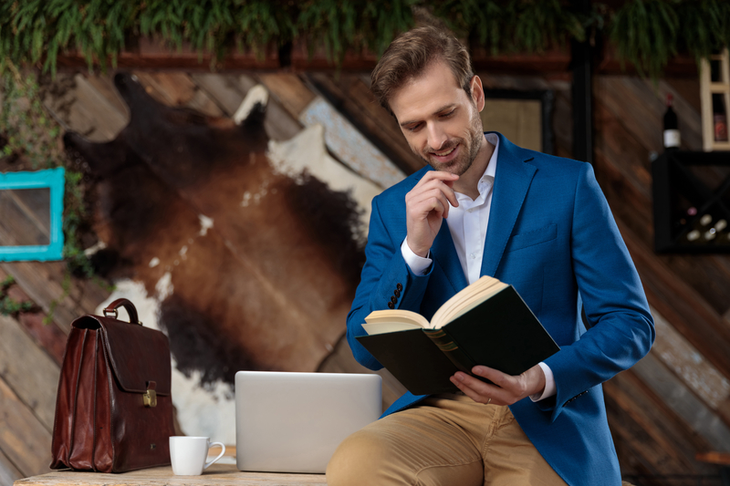 Businessman reading a book with his hand on his chin