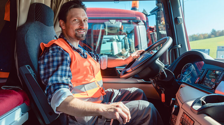 Lorry or truck driver sitting in the cabin of his vehicle