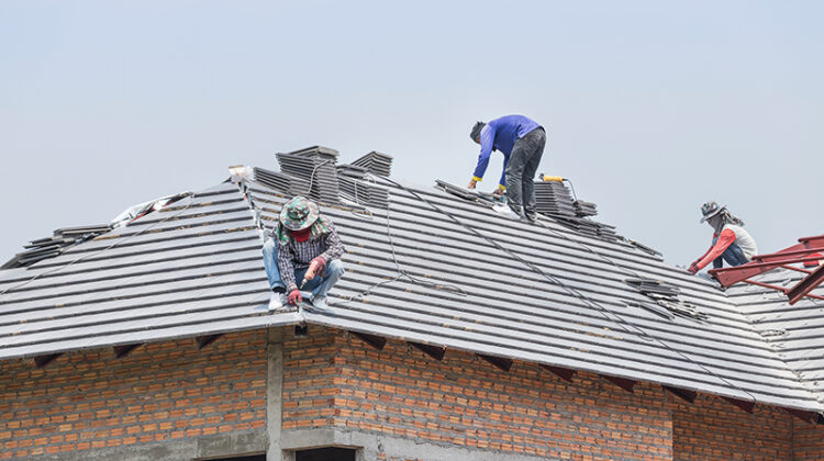 Workers installing concrete tiles on the roof