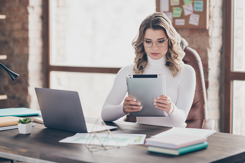 Young female marketer using her Ipad in front of her desk