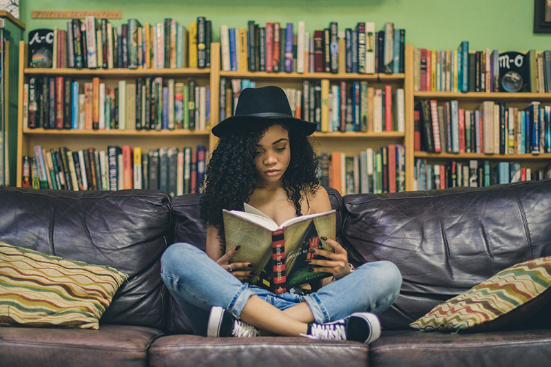 young woman with black hat reading books in the couch