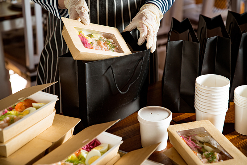 person putting a well-packed food inside the black paper bag