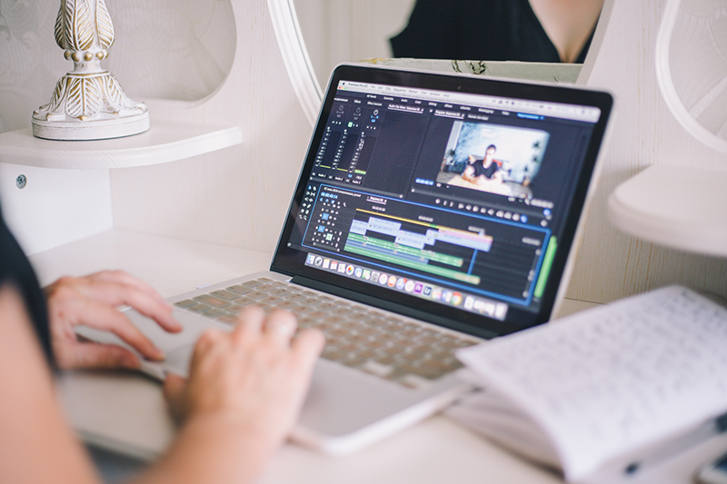 Female hands working on a laptop in a video editing program
