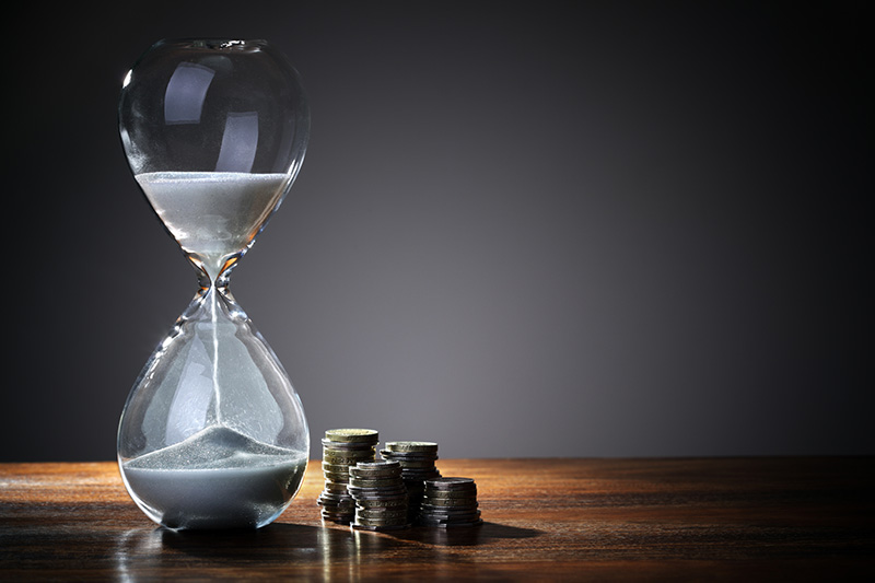Time is money concept with hourglass and British coin currency