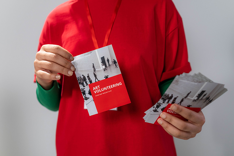phot of a woman in a red long sleeves holding a leaflet