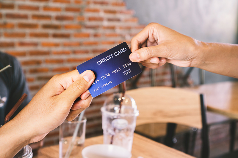Man hand paying his drinks by credit card in coffee shop