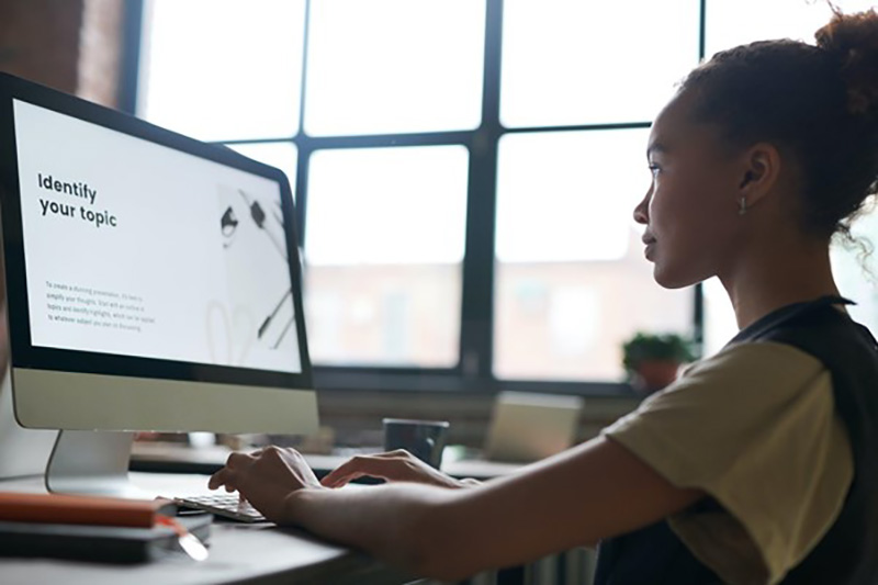 Young woman working in front of Macbook computer