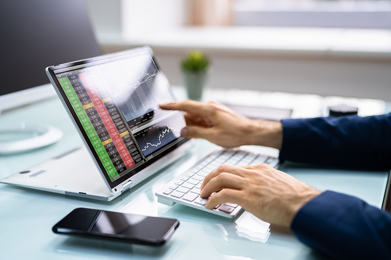 Person working on trading platform on his laptop