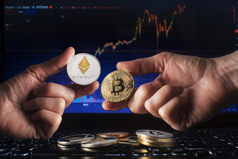 Cryptocurrency concept with hands holding bitcoin and ethereum coin
