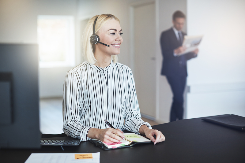 Smiling businesswoman checking her day planner in an office