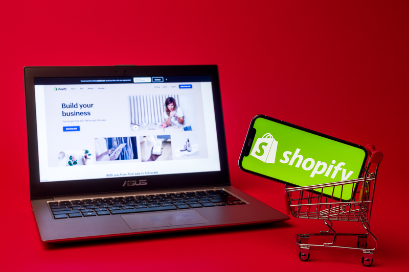 Shopify web page displayed on a modern laptop on red background. Shopify logo on iphone X in shopping cart