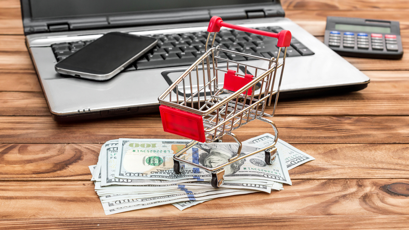Shopping cart with money and credit card, laptop and smartphone on the table.