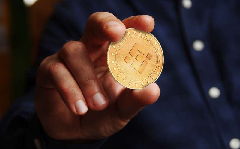 Binance BNB cryptocurrency symbol golden coin in hand abstract concept