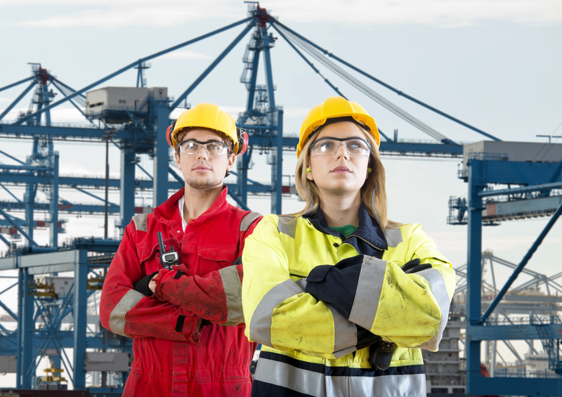 Two tough looking dockers in safety clothing posing in front of a huge container terminal