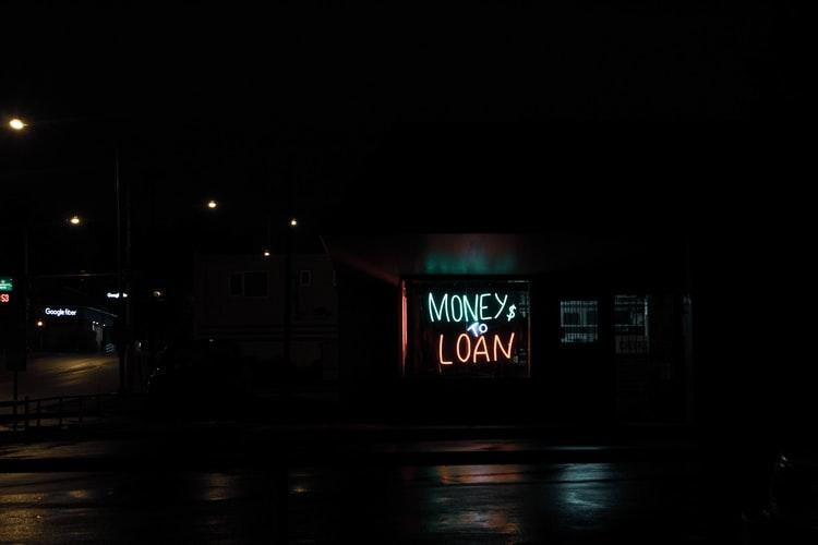 night scene with neon lights signage of money and loan
