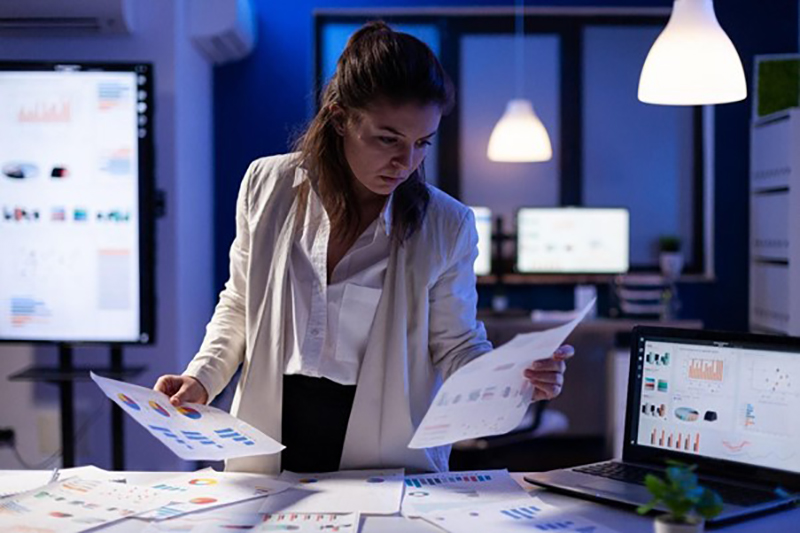 Woman in white coat looking at the graph printed in bond paper