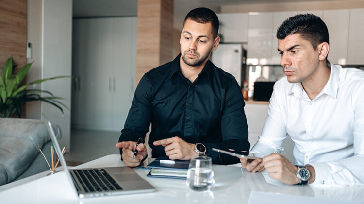 two businessmen having conversation holding pen and macbook pro