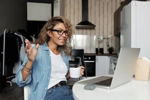a girl holding a mug talking via video call on her laptop
