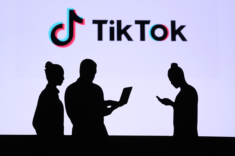 Tiktok logo and 3 shadow of people exchanging messages