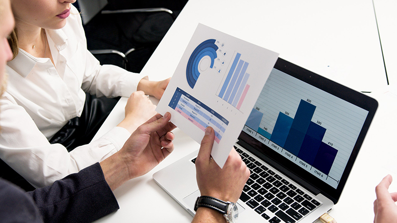 Person holding white paper with graph