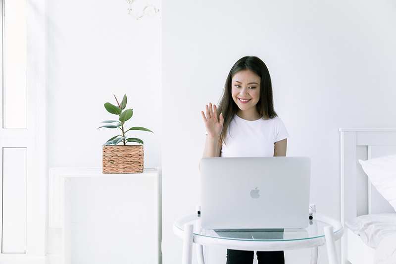 Woman waving in front of her laptop