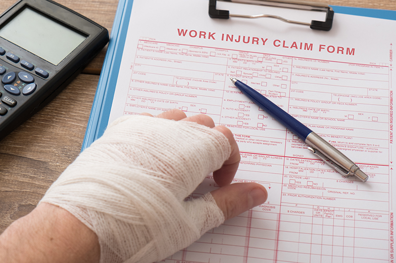 Person with hand injured filing work injury claim form