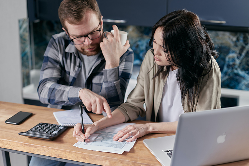 man and woman calculating bills with calculator and laptop in front of them