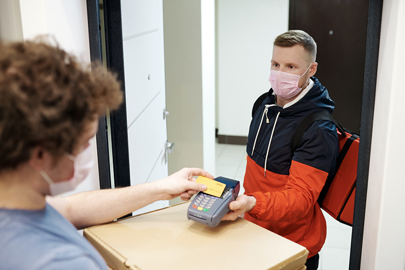 Person wearing facemask while paying the delivery
