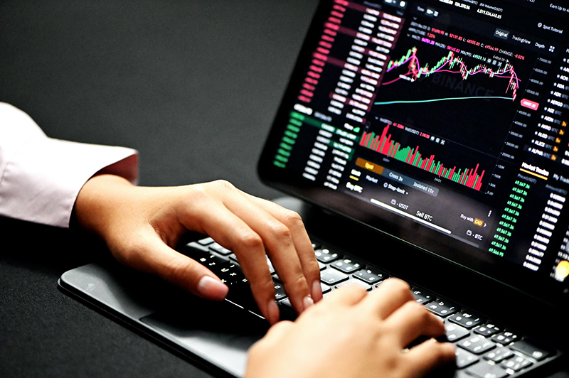 Person using laptop with trading graph chart
