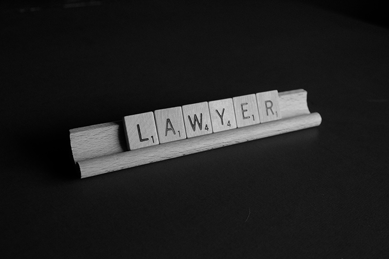 brown wooden scrabble on black background with word formed lawyer