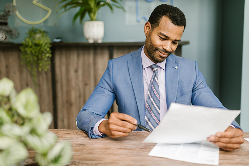 man in blue suite jacket holding white paper