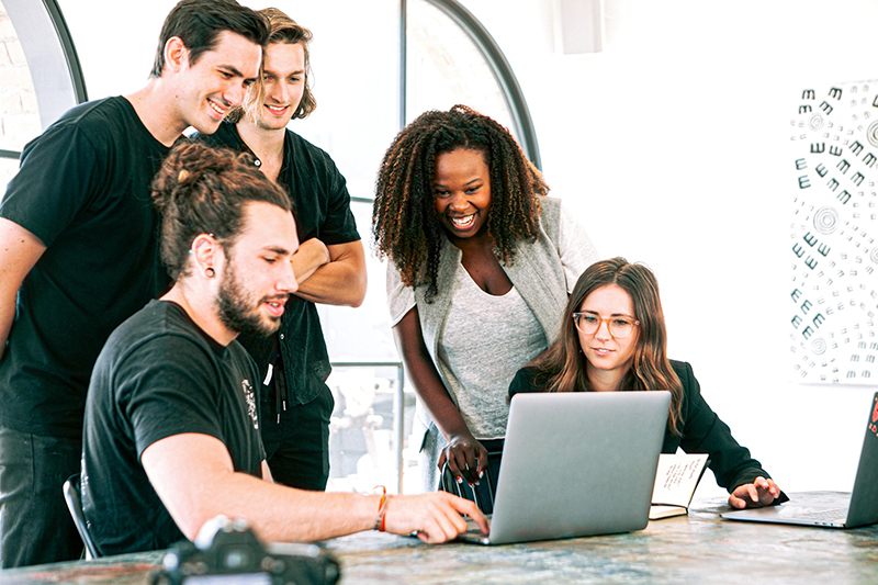 Group of people in front of silver laptop