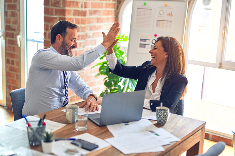 Two middle age business workers with smile on face hand giving high five at the office