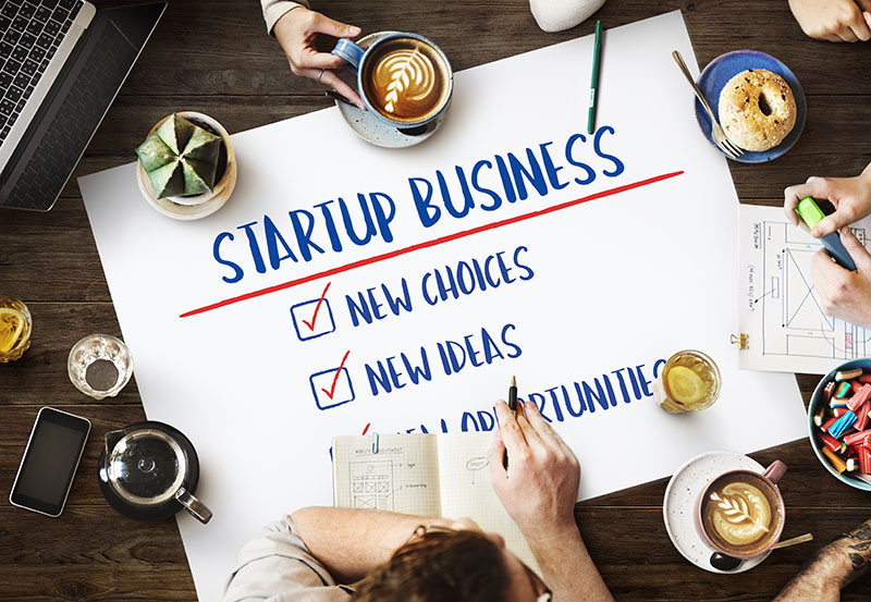startup business written on the white paper placed on the table