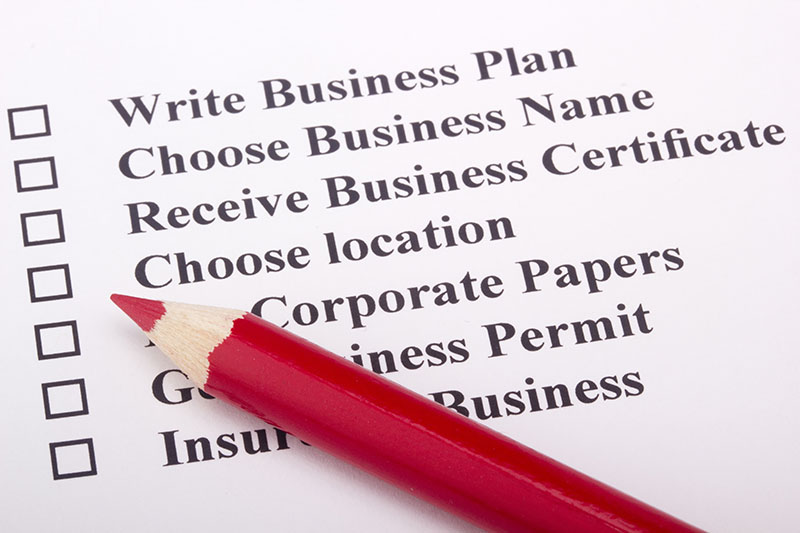 A red pencil laying on a paper with a checklist for starting a business.