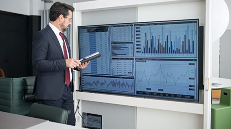 Businessman standing near big screen with trading graphs