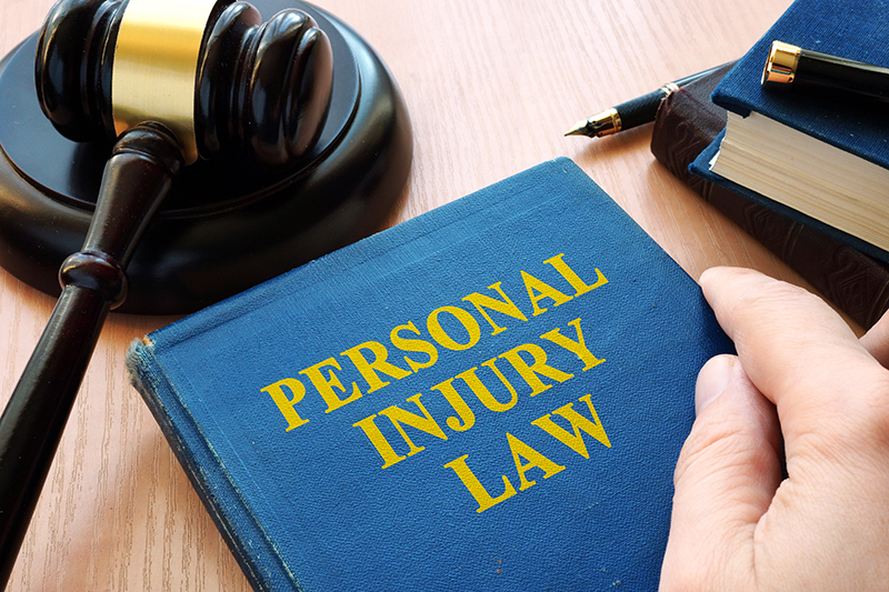 Personal injury law book and judge hammer