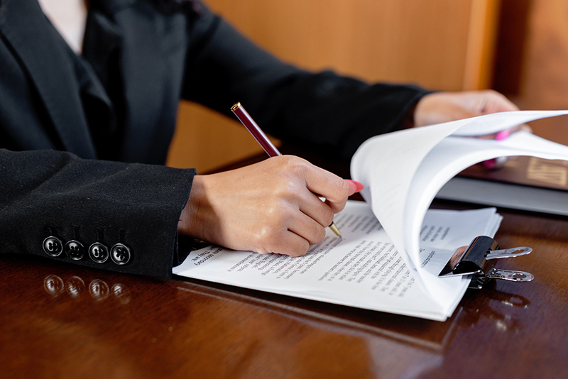 Man in black suit signing a documents