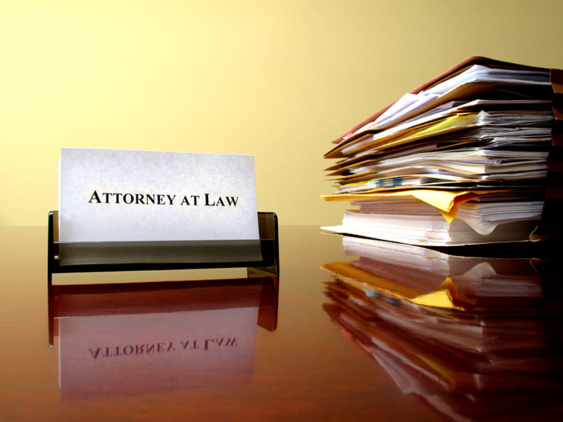 attorney at law signage near the pile of documents