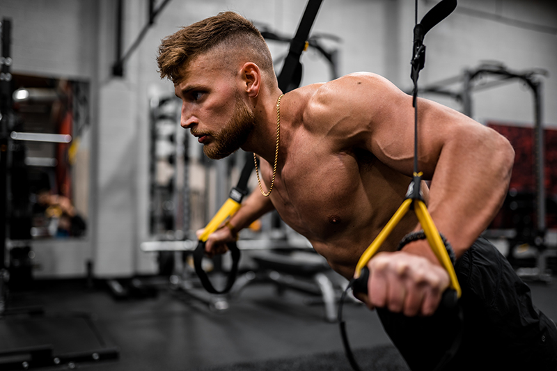 topless man in black pants holding black and yellow exercise equipment