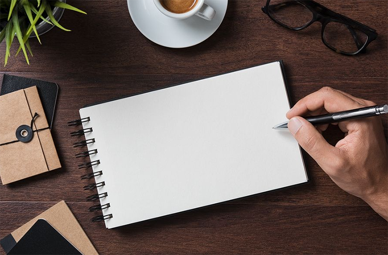 White notebook on top of brown wooden table