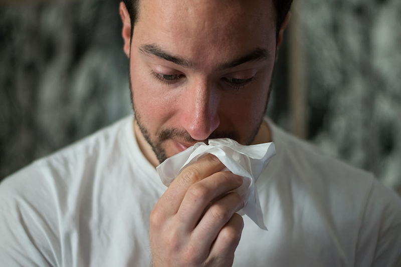 Man wiping mouth with tissue