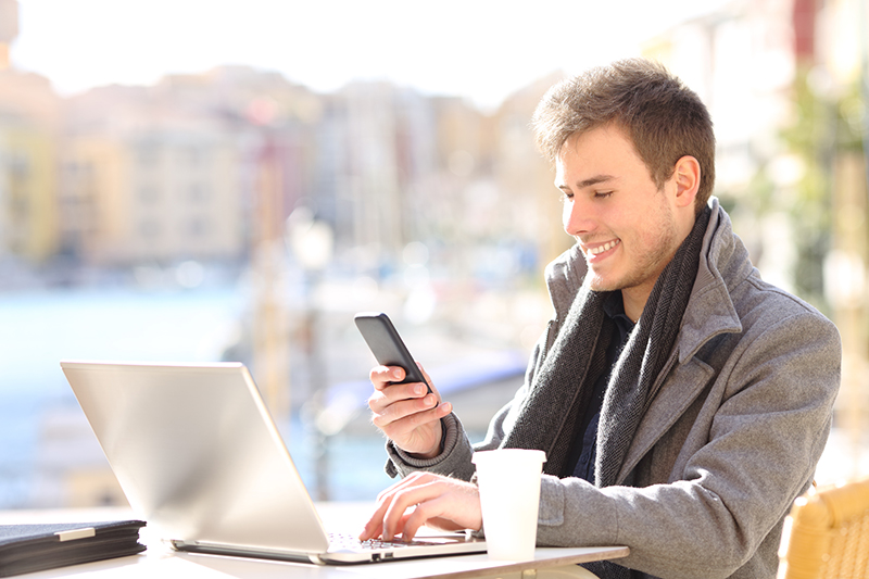 Young man smiling while using his mobile phone and laptop