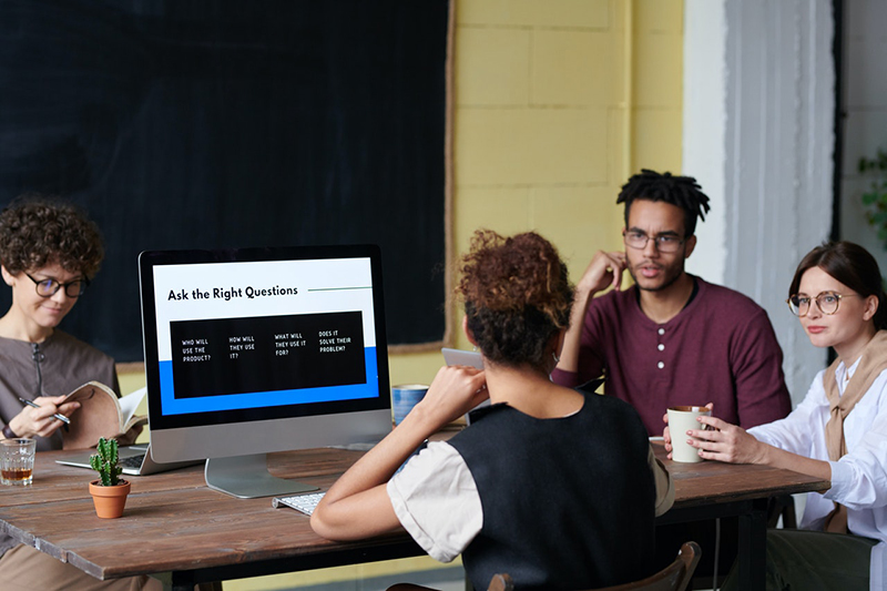 Four people talking near computer