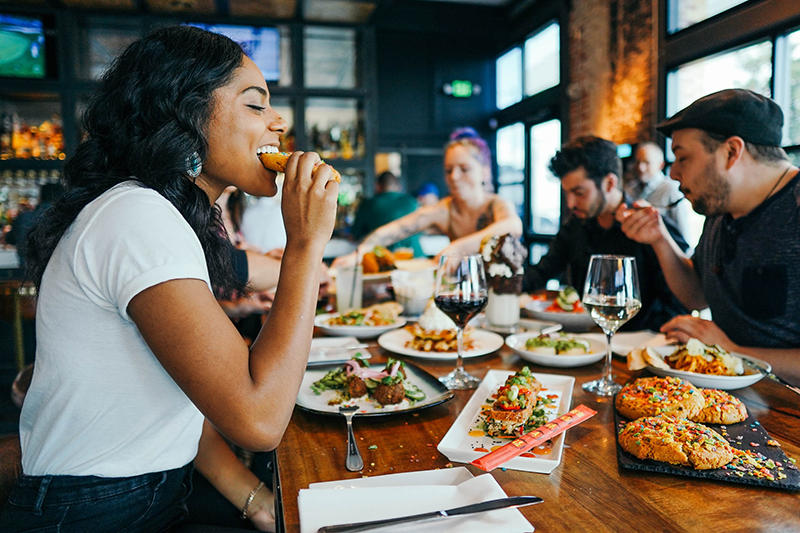 Woman in white shirt eating in a restaurant