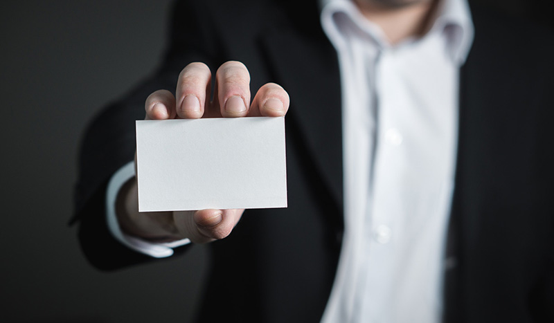 Person holding blank business card