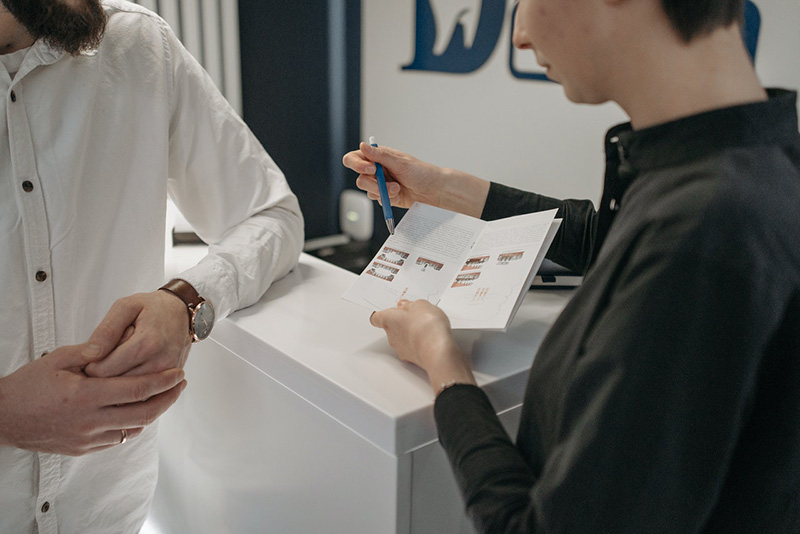 Woman showing brochure to colleague